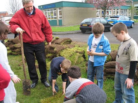 Building a Mesolithic hut. St Malachy's pupils cut turf sods for the walls.
