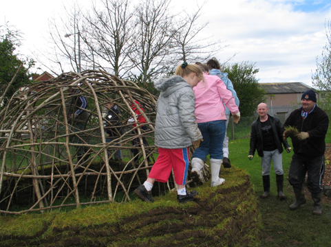 Building a Mesolithic hut. St Malachy's pupils start to build up the walls.